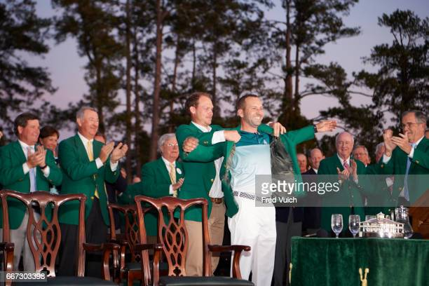 The Masters Sergio Garcia victorious putting on green jacket with Danny Willett's help during ceremony after Sunday play at Augusta National Augusta...