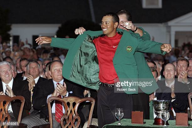 Golf The Masters Tiger Woods victorious putting on green blazer with Phil Mickelson after winning playoff and tournament vs Chris DiMarco on Sunday...
