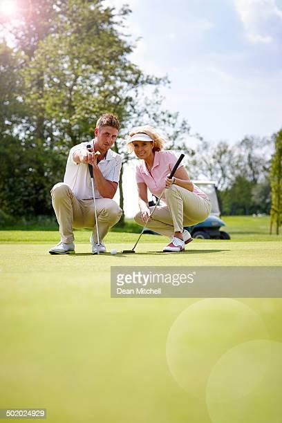 Golf trainer teaching woman putting