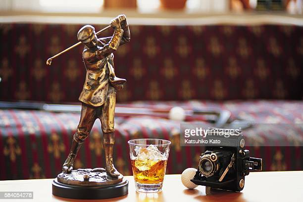 A Golf Trophy and Whiskey on a Table
