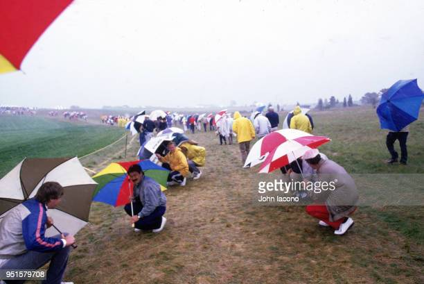 US Open Fans taking cover with umbrellas during rain delay during Thursday play at Shinnecock Hills Golf Club Southampton NY CREDIT John Iacono