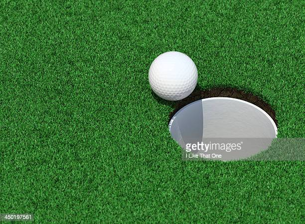 golfball on the lip of the cup / golf hole - putting green stock pictures, royalty-free photos & images