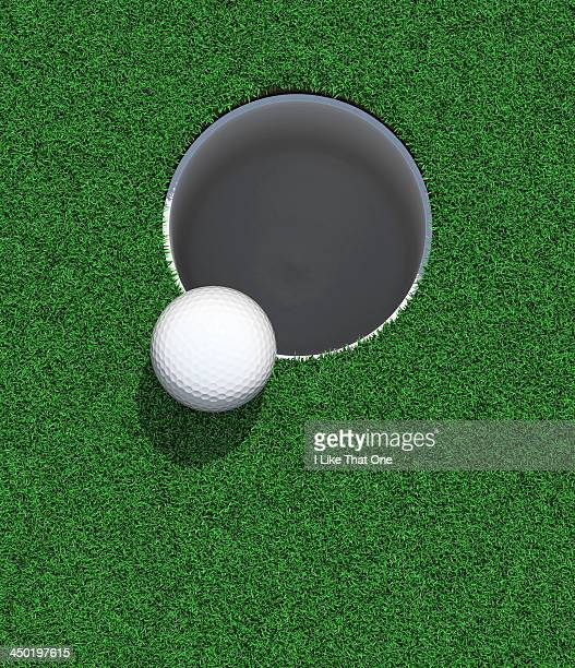 golfball on the lip of the cup / hole - 穴 ストックフォトと画像