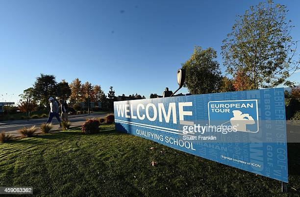 A golfer and caddie walk past the welcome sign prior to the second round of the European Tour qualifying school final stage at PGA Catalunya Resort...