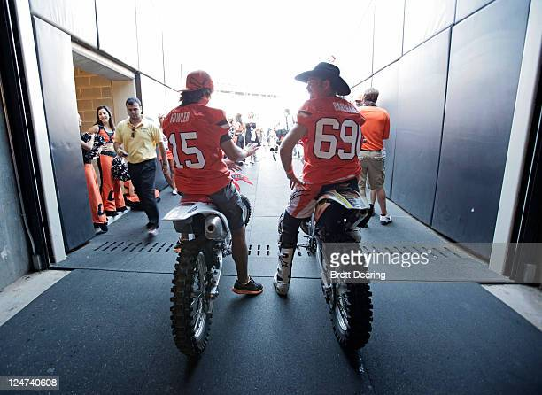 PGA golfer and former Oklahoma State Cowboy Rickie Fowler left and professional motocross rider 'Cowboy' Kenny Bartram wait to ride on the field...