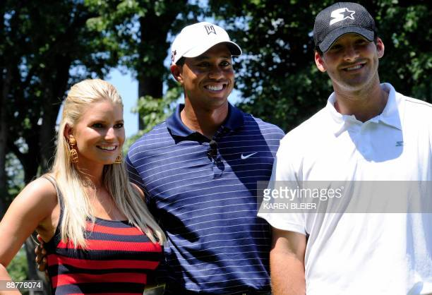 US golfer and tournament host Tiger Woods poses for photos with Dallas Cowboys quarterback Tony Romo and entertainer Jessica Simpson during opening...