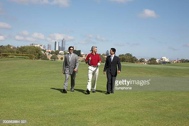 Golfer and two businessmen walking on golf course