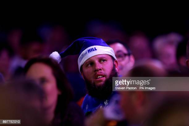Golfer Andrew Johnston watches Phil Taylor play during day ten of the William Hill World Darts Championship at Alexandra Palace London