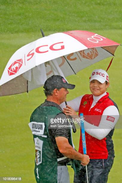 LPGA golfer Ariya Jutanugarn waits to putt on the 18th green as heavy rains fall during the second round of the Indy Women In Tech on August 17 2018...