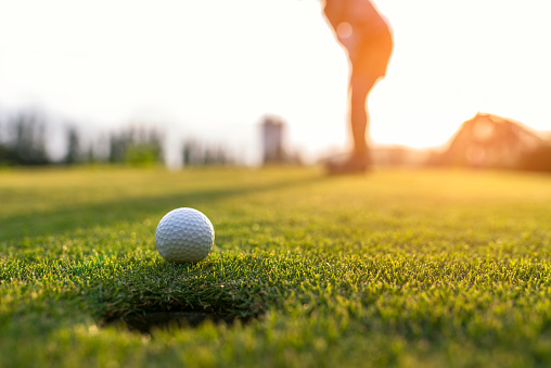 Golfer asian woman putting golf ball on the green golf on sun set evening time, select focus. Healthy and Lifestyle Concept. 887491304