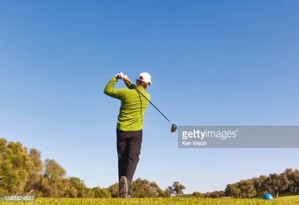 golfer at end of swing. - ティーショット ストックフォトと画像