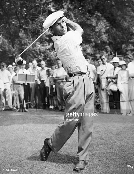 Golfer Ben Hogan follows through on a swing before a field of spectators