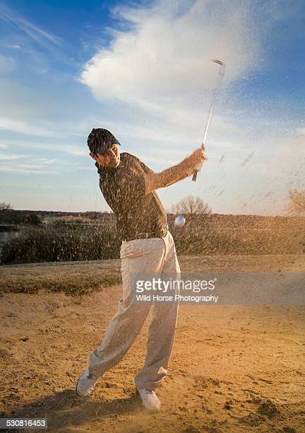 golfer blasting out of sand trap golf