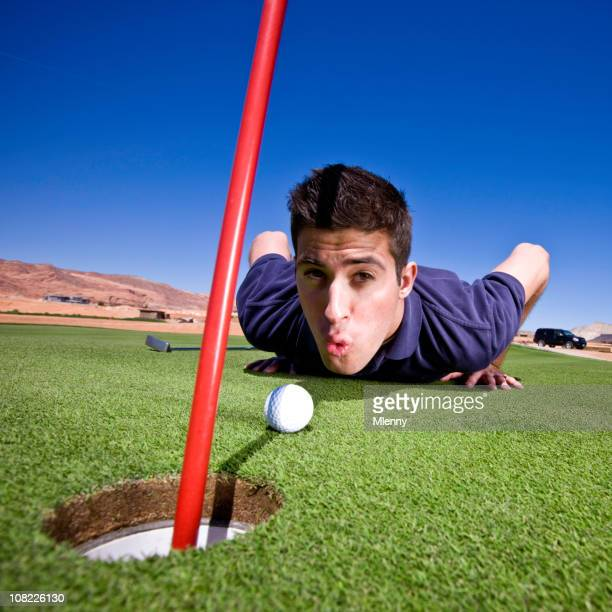 Golfer Blowing Ball into Hole
