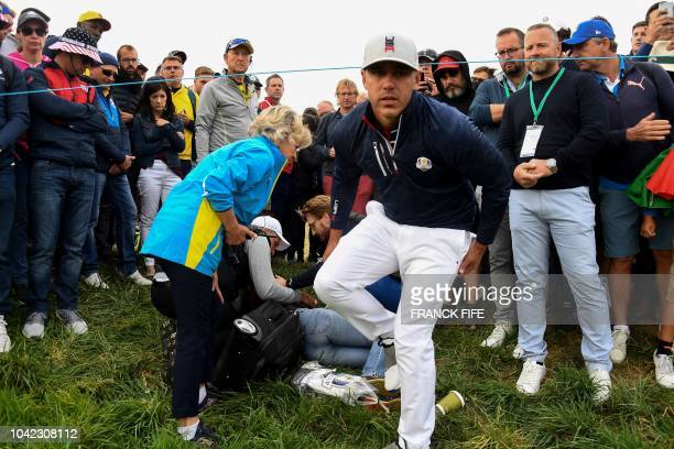 TOPSHOT US golfer Brooks Koepka reacts next to injured spectator Corine Remande who was struck by his tee shot during his fourball match on the first...