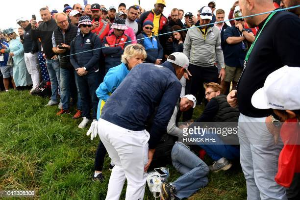 US golfer Brooks Koepka reacts next to injured spectator Corine Remande who was struck by his tee shot during his fourball match on the first day of...