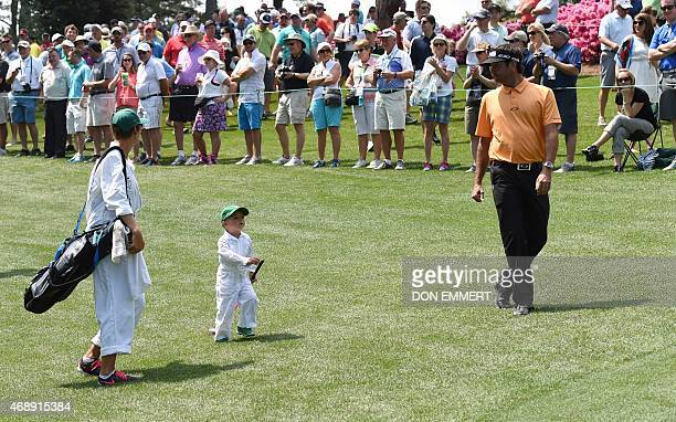 Golfer Bubba Watson with son Caleb and wife Angie walk the fairway during the Par 3 competition on April 8 at Augusta National Golf Club in Augusta,...