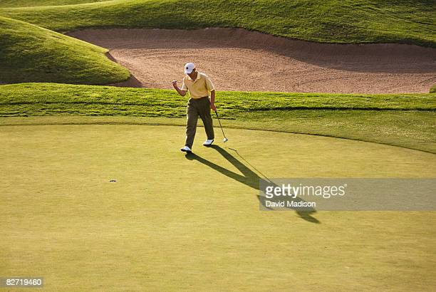 golfer celebrating making putt - golfer stock pictures, royalty-free photos & images