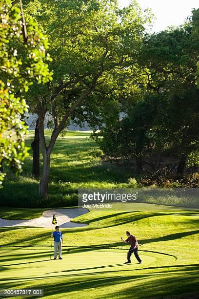 Golfer celebrating shot while partner holds flagstick