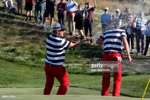 Golfer Charley Hoffman sprays Daniel Berger with champagne on the 17th hole after USA clinches winning the Presidents Cup during the final round of...