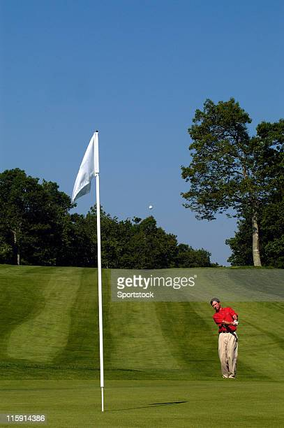 golfer chipping onto green - chip shot stock pictures, royalty-free photos & images