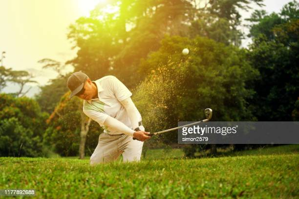 golfer chipping out of sand trap - putting green stock pictures, royalty-free photos & images