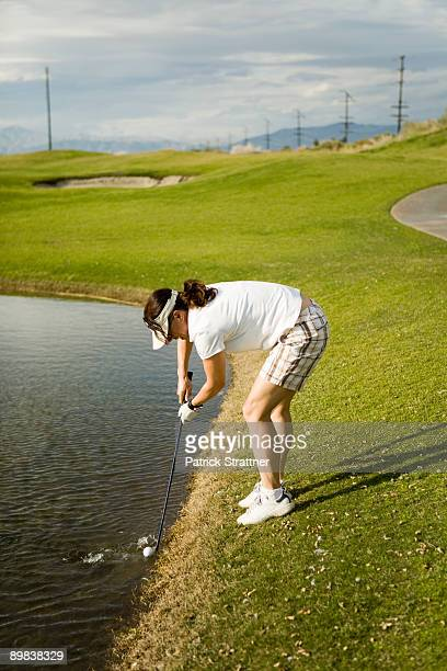 A golfer collecting a golf ball from a water trap