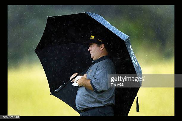 Golfer Craig Parry shelters under his umbrella as the skies open at the Australian Open 18 December 2003 THE AGE Picture by RAY KENNEDY
