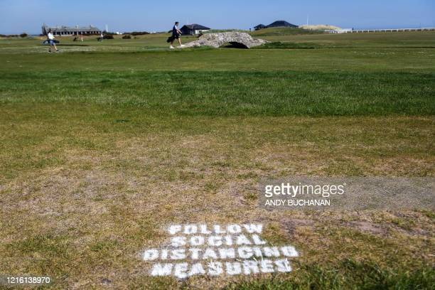 Golfer crosses the iconic Swilcan Bridge with a sign on the grass reminding golfers to respect social distancing measures at The Old Course in St...