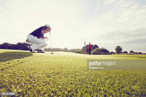 Golfer crouching on course, Korschenbroich, Dusseldorf, Germany