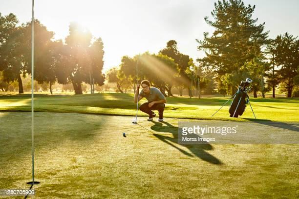 golfer crouching while analyzing on golf field - パッティンググリーン ストックフォトと画像