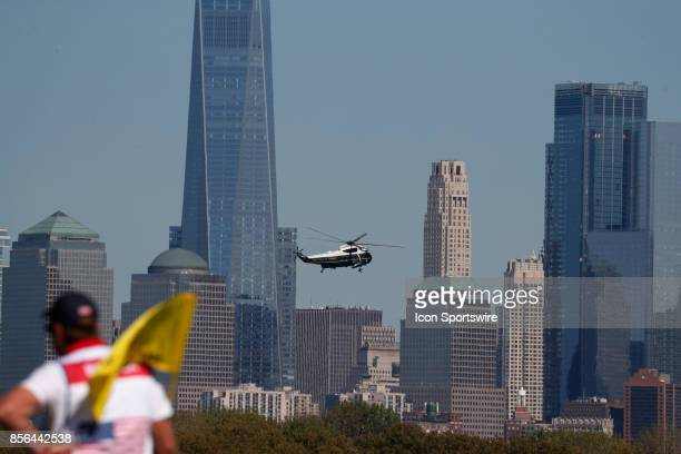 Golfer Daniel Berger putts on the 10th hole as the presidential helicopter flies over the Manhattan skyline as Donald Trump the 45th president of the...