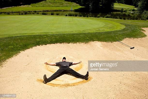 golfer doing sand angeles. - golf lustig stock-fotos und bilder