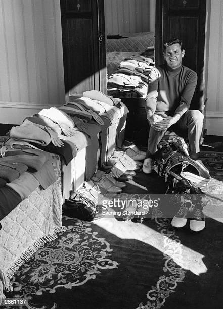 Golfer Doug Sanders sitting in his dressing room surrounded by the outfits he wore at Hoylake