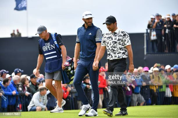 Golfer Dustin Johnson and Australia's Jason Day walk up the fairway from the first hole during the first round of the British Open golf Championships...
