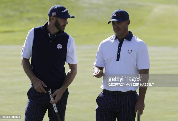 US golfer Dustin Johnson and US golfer Brooks Koepka speak during their foursomes match on the second day of the 42nd Ryder Cup at Le Golf National...