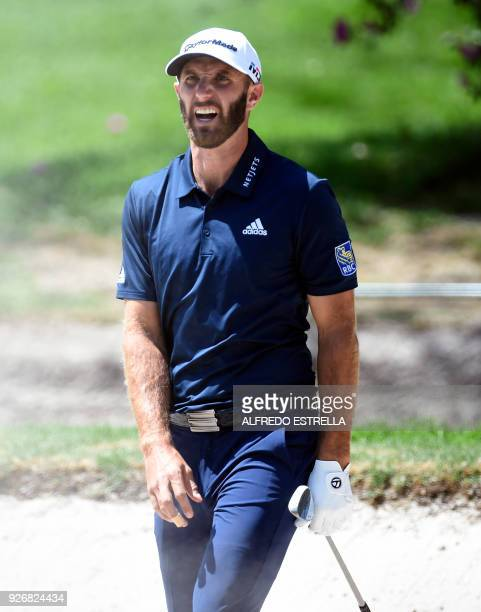 US golfer Dustin Johnson gestures after playing his shot from a bunker at the first green during the third round of the World Golf Championship in...