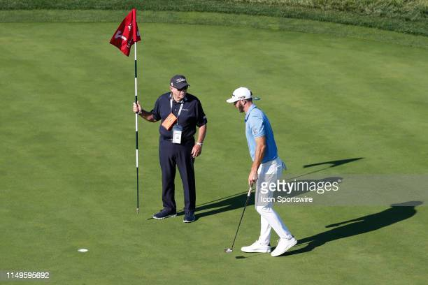 Golfer Dustin Johnson gets putting instruction from his coach Butch Harmon on the 7th hole during the practice round for the 2019 US Open on June 11...
