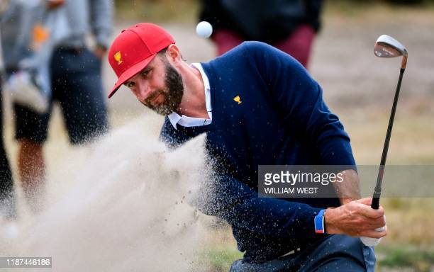 US golfer Dustin Johnson hits out of a bunker during a practice round ahead of the Presidents Cup golf tournament starting on December 12 in...