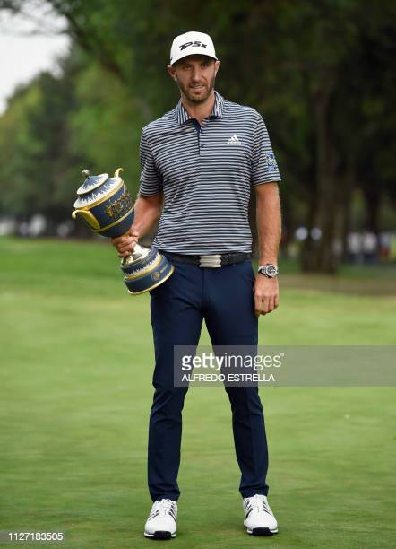 US golfer Dustin Johnson poses with the trophy after winning the World Golf Championship at Chapultepec's Golf Club in Mexico City on February 24 2019