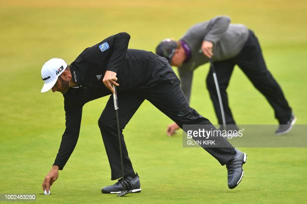 Golfer Dustin Johnson retrieves his ball as US golfer Charley Hoffman places his, on the 18th green during their second rounds on day 2 of The 147th...