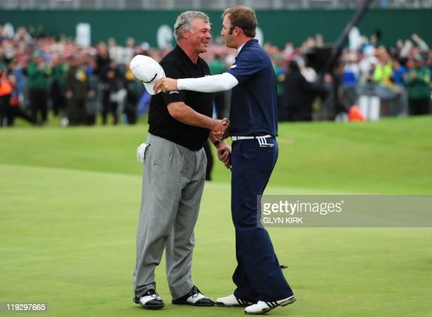 US golfer Dustin Johnson shakes hands Northern Irish golfer Darren Clarke on the 18th green after Clarke won the 140th British Open Golf championship...