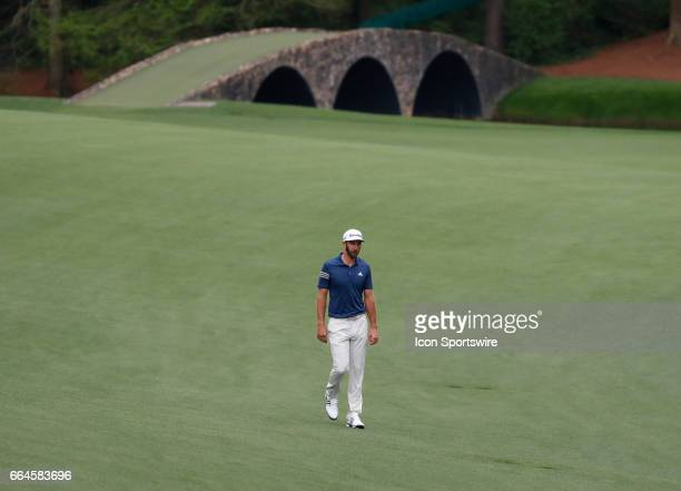 PGA golfer Dustin Johnson walks the 13th fairway as the Hogan Bridge is in the background during the first day of practice for the 2017 Masters...