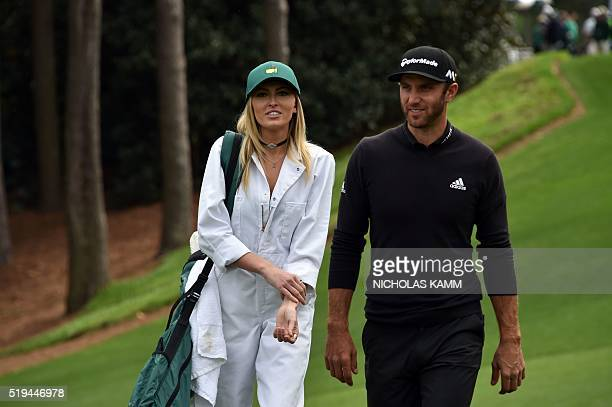 US golfer Dustin Johnson walks with Paulina Gretzky down the 1st fairway during the Par 3 contest prior to the start of the 80th Masters of...