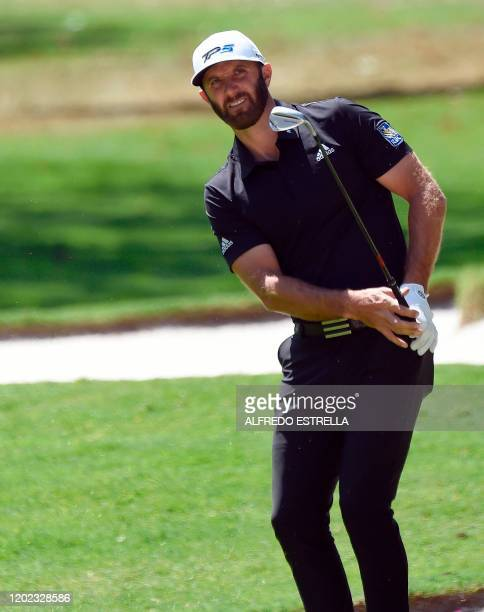 US golfer Dustin Johnson watches his approach shot to the1st green during the second round of the World Golf Championship at Chapultepec's Golf Club...