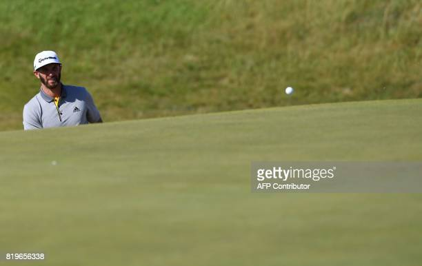 US golfer Dustin Johnson watches his chip land on the 9th green during his opening round on the first day of the Open Golf Championship at Royal...