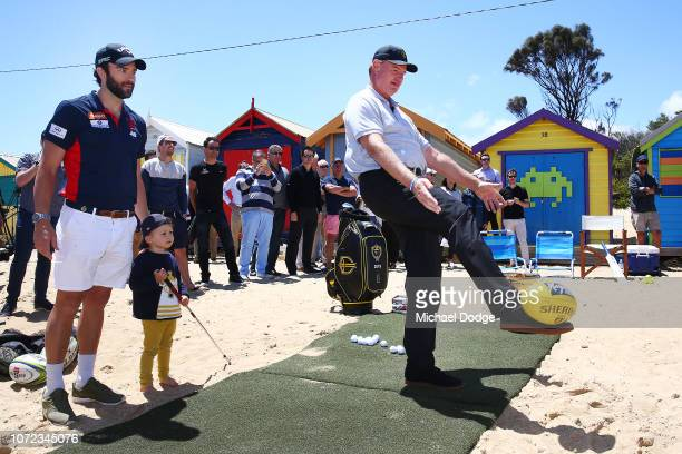Golfer Ernie Els of South Africa watched by Melbourne Demons' Jordan Lewis kick an Australian Rules football at a target during The Big Easy's BBQ at...