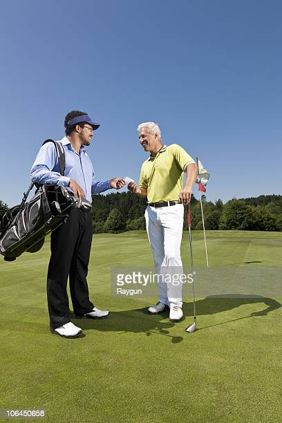 Golfer giving his card to the caddy