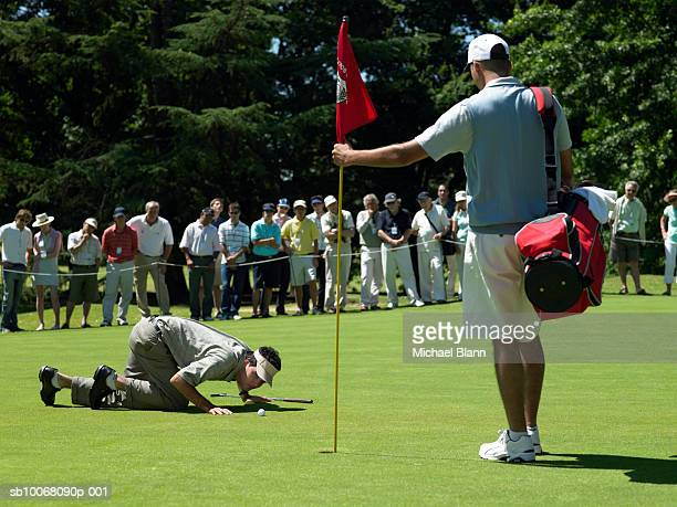 Golfer having close look at ball on course