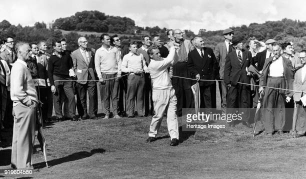 Golfer hitting a drive 19581961 A professional golfer in full swing during a golf tournament on an unidentified English course A caddy to the left is...